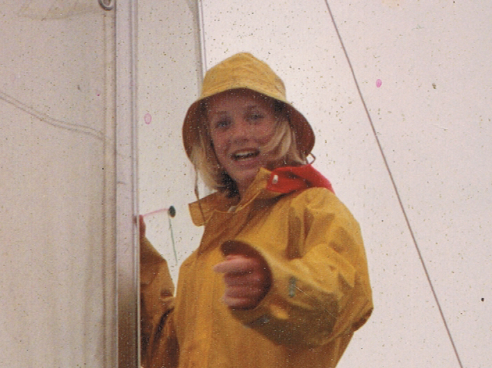 Girl in rain gear next to mast of yacht