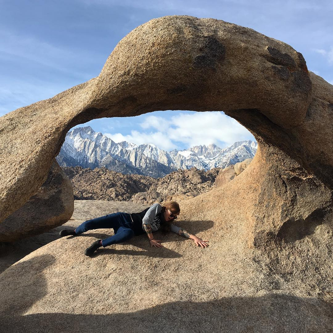 person laying under rock arch