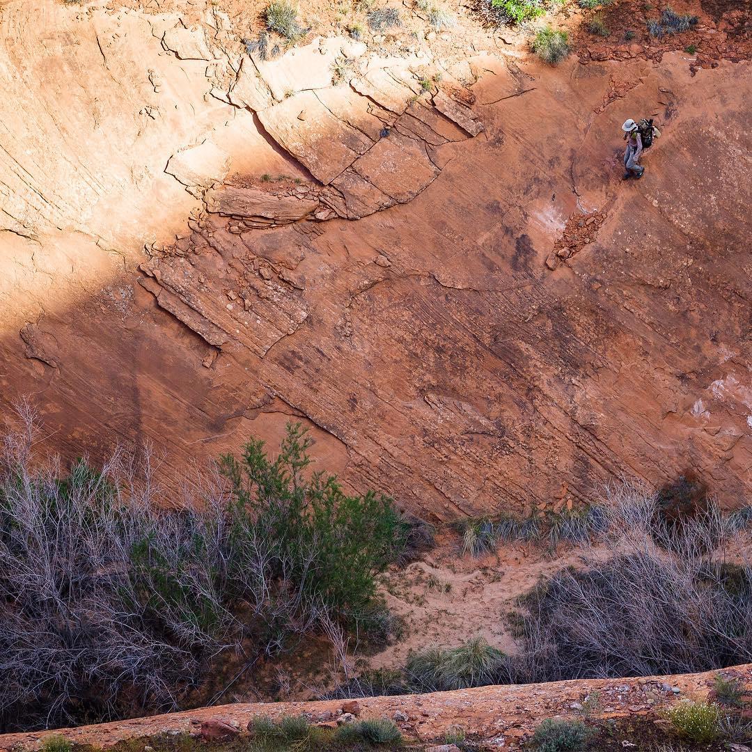 woman walking on red rock wall