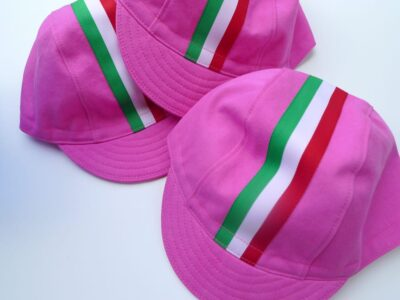 Three bright pink cycling caps with italian flag ribbon