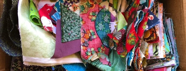Cardboard box with colorful quilting cotton scraps inside